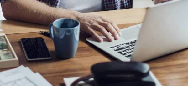 a man on a laptop with a mug working on a desk