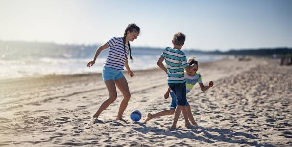 three kids playing soccer on the beach near the water